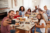 Two Families Taking Selfie As They Enjoy Meal At Home Together