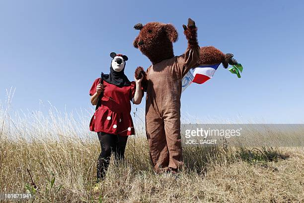 Two fans dressed up as Mickey and a red squirrel with a French flag pose in a field as they wait for the riders at the Passage du Gois prior to the...