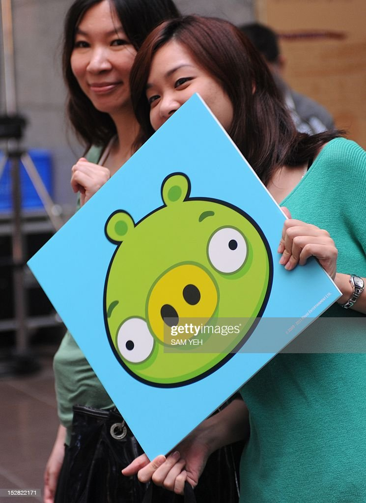 Two fans hold a Bad Piggies placard from the Angry Birds game during a press conference in Taipei on September 27, 2012. 'Angry Birds' maker Rovio is to launch a new title allowing users to play as the 'Bad Piggies' from the smash-hit game, and take revenge on the birds who attacked them with slingshots. AFP PHOTO / Sam Yeh