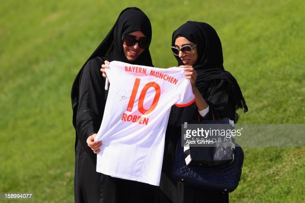 Two fans hold a shirt of Arjen Robben during a Bayern Muenchen training session at the ASPIRE Academy for Sports Excellence on January 5 2013 in Doha...