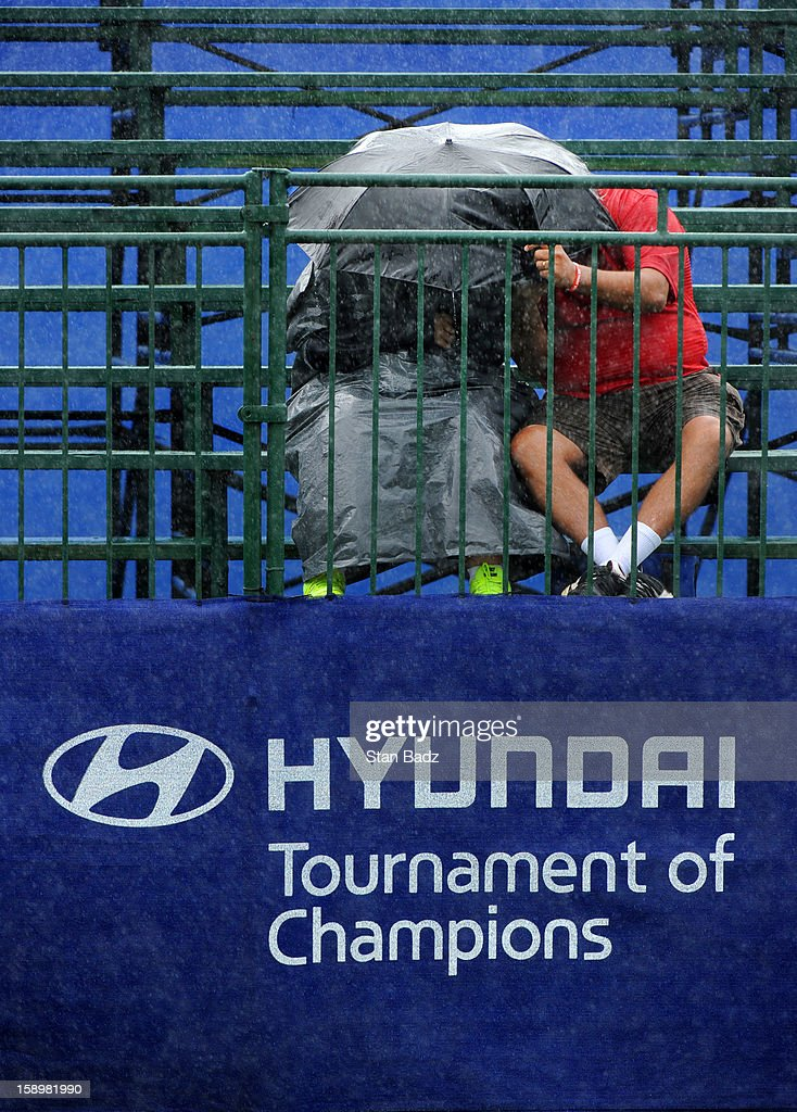 Two fans huddle for cover from the rain on the first hole during the first round of the Hyundai Tournament of Champions at Plantation Course at Kapalua on January 4, 2013 in Kapalua, Hawaii.