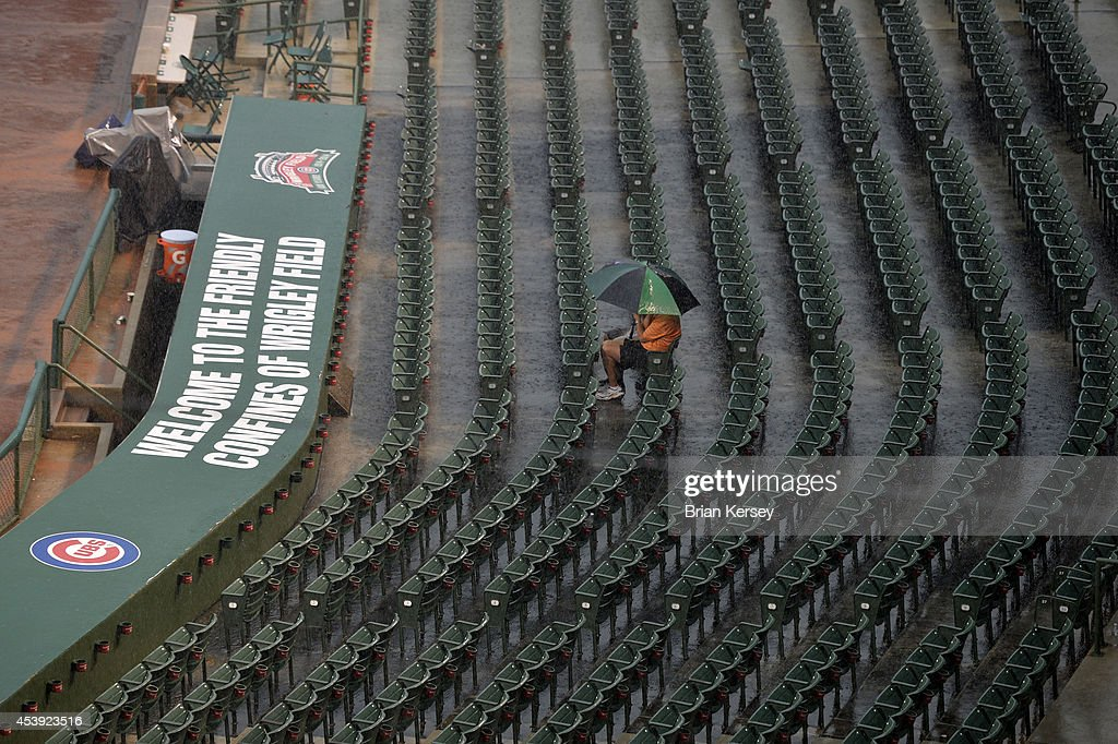 Two fans huddle under an umbrella as rain falls, delaying the restart of a suspended game from August 19 between the Chicago Cubs and the San Francisco Giants at Wrigley Field on August 21, 2014 in Chicago, Illinois. The game was initially called off in the early morning hours of August 20, but Major League Baseball accepted the Giants' appeal, ruling the delay was caused by a mechanical failure of the tarp and changing the status of the game from cancelled and completed with a Cubs 2-0 win to a suspended game. The Cubs and Giants hope to finish the game before their regularly scheduled game today.