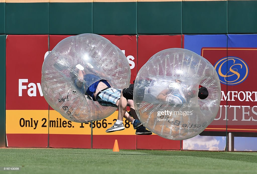 Two fans inside inflatable balls crash into each other in left field between innings of a spring training game between the Arizona Diamondbacks and...