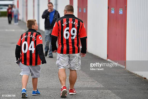 Two fans make their way to the stadium during the Premier League match between AFC Bournemouth and Everton at the Vitality Stadium on September 24...