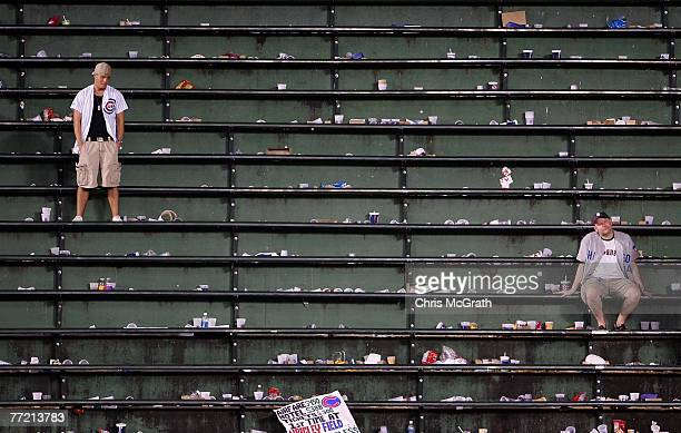 Two fans of the Chicago Cubs remain in the bleachers as they look dejected after the Cubs lost 51 against the Arizona Diamondbacks during Game Three...