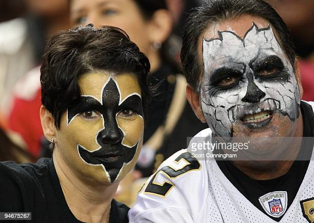 Two fans of the New Orleans Saints wear face paint as they watch the play against the Atlanta Falcons at the Georgia Dome on December 13 2009 in...