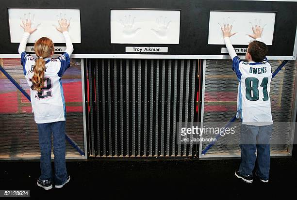 Two fans place their hands on an exhibit measuring NFL hand sizes during the NFL Experience prior to the start of Super Bowl XXXIX on February 3 2005...