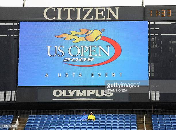 Two fans sit below the scoreboard in Arthur Ashe Stadium as rain delays the US Open at the USTA Billie Jean King National Tennis Center September 11...