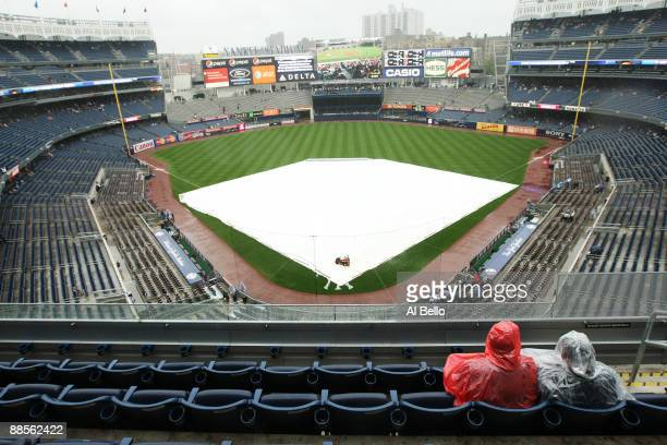 Two fans sit during a rain delay before the game between the New York Yankees and the Washington Nationals on June 18 2009 at Yankee Stadium in the...