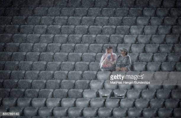 Two fans sit in the rain during the halftime break of the Bundesliga match between FC Bayern Muenchen and Bayer 04 Leverkusen at Allianz Arena on...