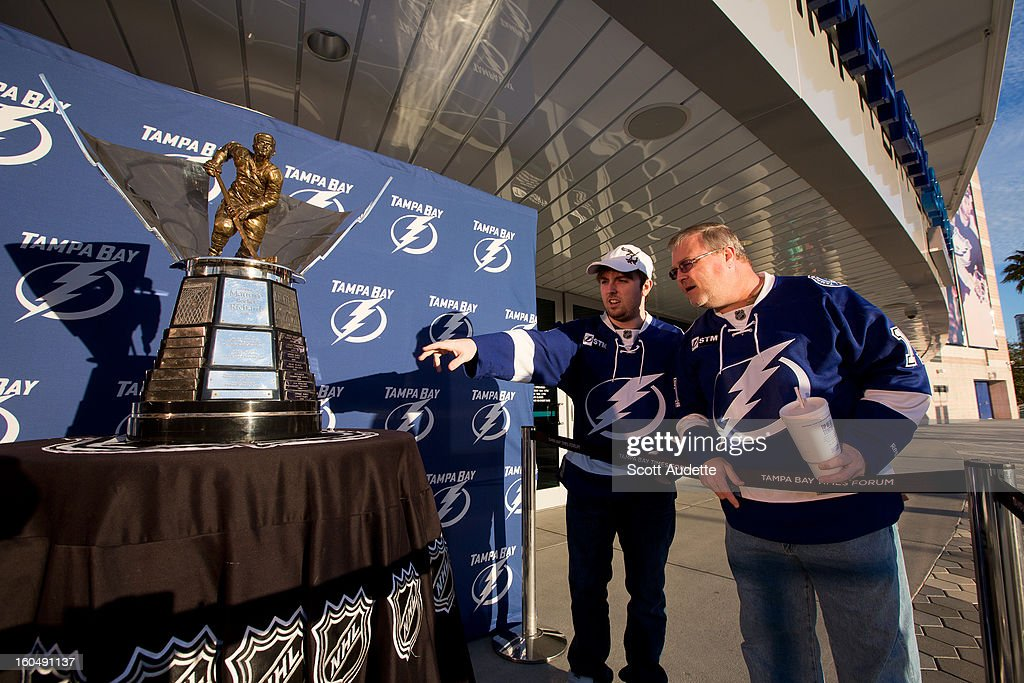 Two fans stand beside the Maurice 'Rocket' Richard Trophy on February 1, 2013 at Tampa Bay Times Forum in Tampa, Florida. The trophy was awarded to Steven Stamkos #91 of the Tampa Bay Lightning for the 2011-12 season.