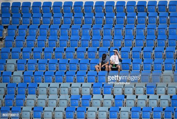 Two fans wait for the start of the 2017 Confederations Cup group B football match between Germany and Cameroon at the Fisht Stadium Stadium in Sochi...