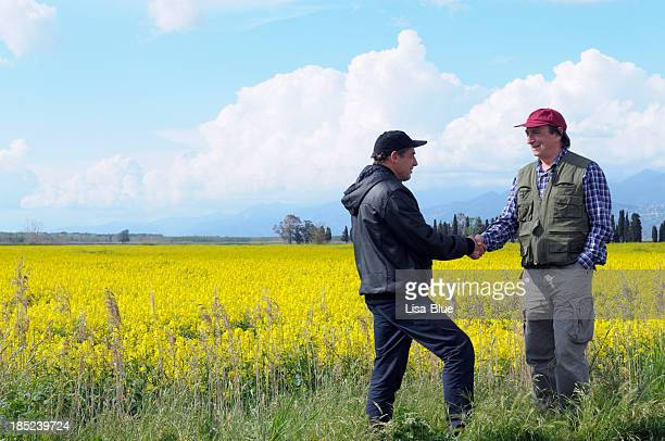 Two Farmers Handshaking in the Countryside