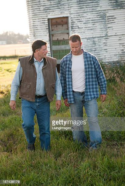 Two farmers walking away from a white barn