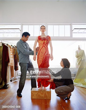 Two fashion designers adjusting female model's (16-18) dress in studio : Stock Photo