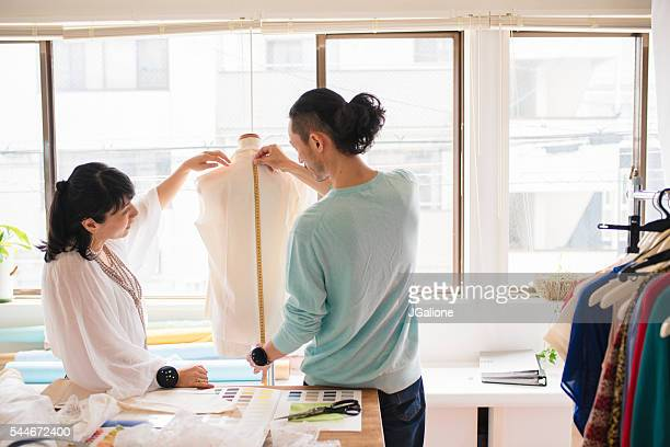 Two fashion designers taking measurements