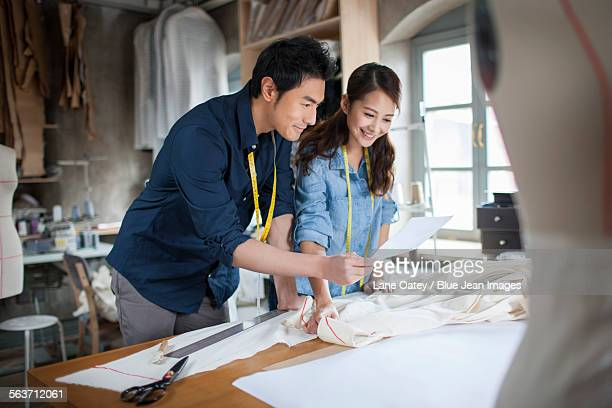 Two fashion designers working in studio