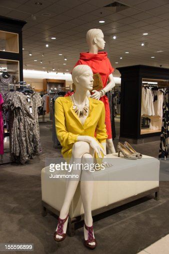 Two fashion mannequins dressed up in a clothing store.
