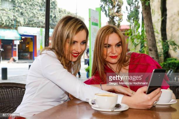 Two fashionable mid adult women in Mexico City taking a selfie in front of their coffee cups