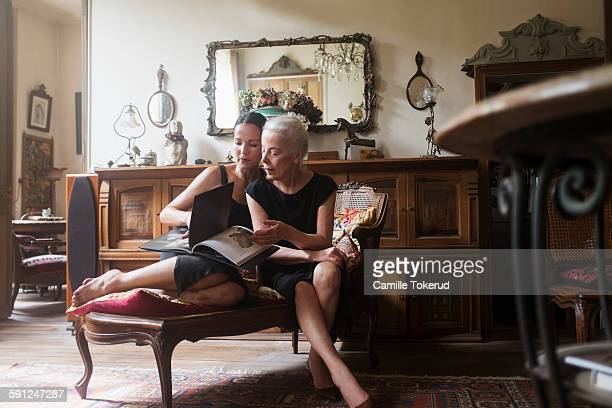 Two fashionable women looking at photograph book