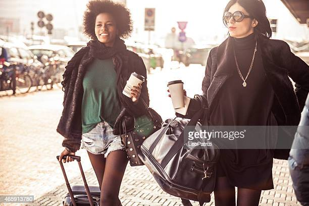 Two fashionable women walking out of the airport
