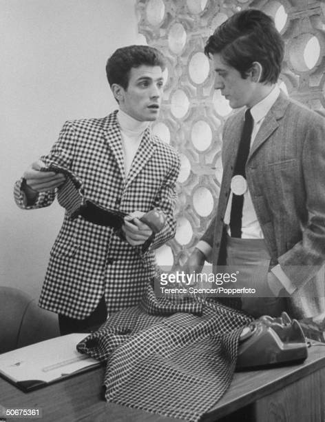Two men talking to each other one wearing a checkered blazer jacket while holding the phone and the other wearing a twopiece suit with one hand in...