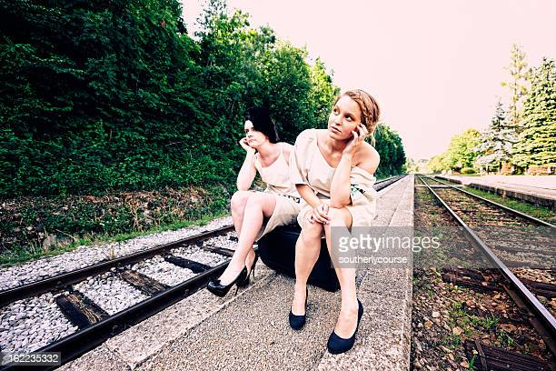 Two Fashionable Young Women Waiting at Train Station