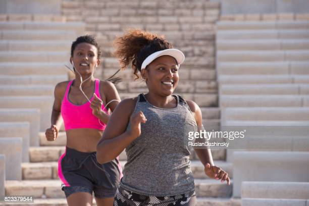 Two fat and thin women running outdoors.