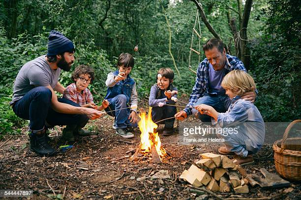 Two fathers and four boys toasting marshmallows on campfire in forest