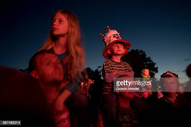 Two fathers with their children on their shoulders enjoy the live performance by The Flaming Lips at Camp Bestival The band are known for their...