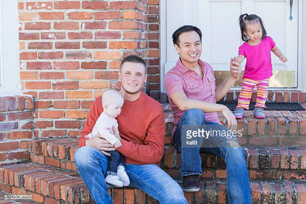 Two fathers with their young children sitting on steps