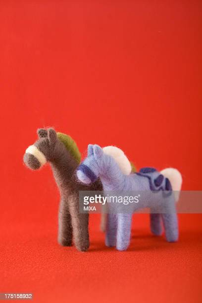 Two Felt Toy Horses on Red Paper