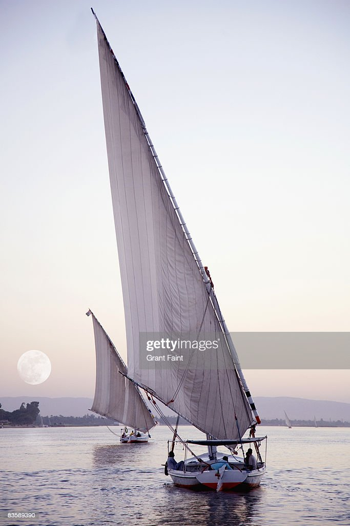 two feluka sailboats on nile river evening dusk