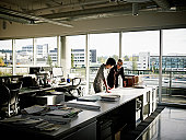 Two female architects examining plans in office