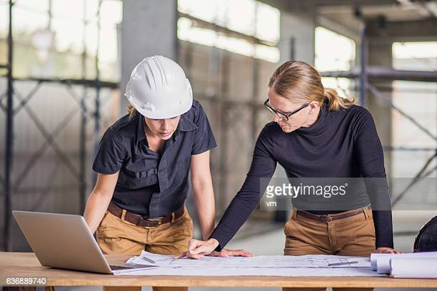 Two female architects reviewing blueprints