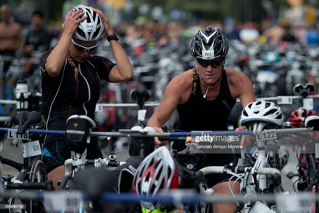 Two female athletes take their bikes at the transition area prior to start the biking course of one of the Age Groupers Wave Race during the ITU World Trathlon on August 24, 2014 in Stockholm, Sweden.