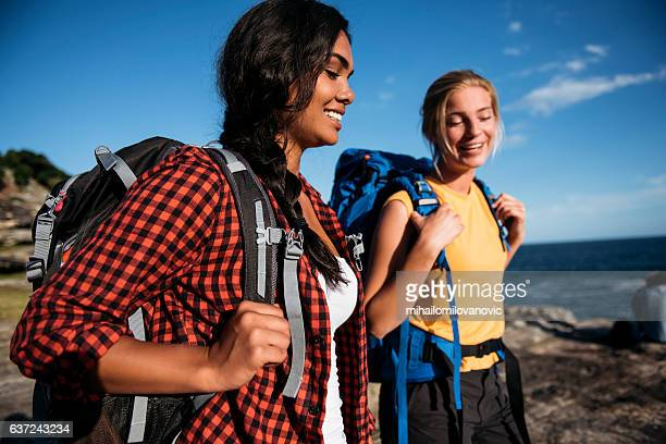 Two female backpackers taking a walk near the ocean