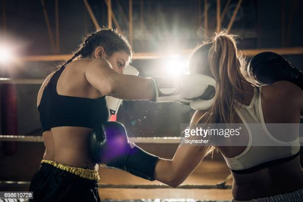 Two female boxers fighting during a boxing match in a ring.