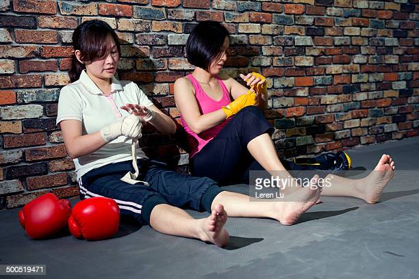 Two female boxers unwrapping hand bandages.