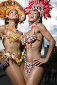 Two female carnival dancers smiling, low angle view