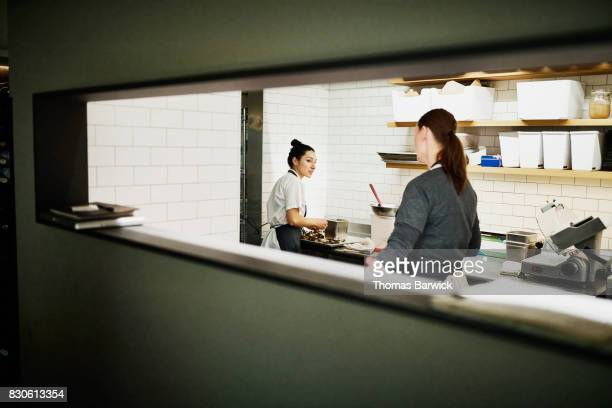 Two female chefs in discussion while preparing for dinner service in restaurant kitchen