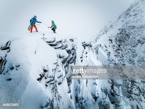 Two female climbers balancing over a snowy ridge