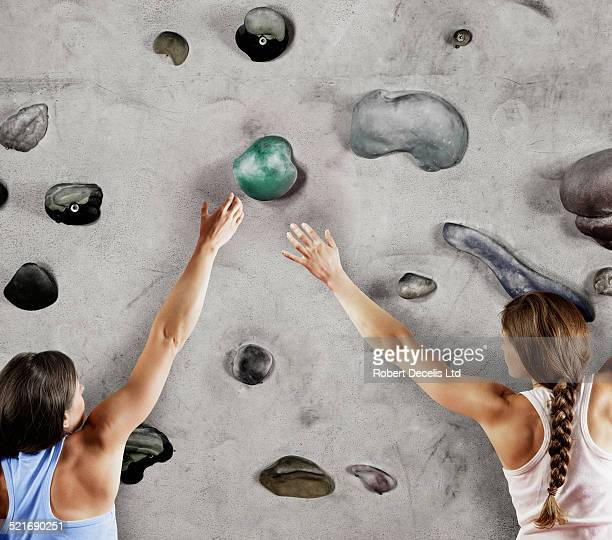 Two female climbers reaching for the same hold