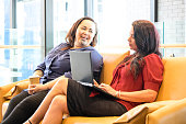 Two female co-workers in modern office interior brainstorming a project; caucasian female is working on laptop computer; Maori employee holds takeaway cup and has tattoos including facial to moko.