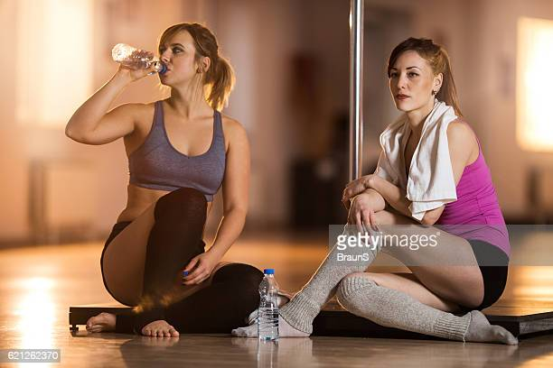 Two female dancers taking a break from pole dancing.