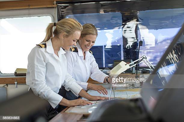 Two female deck officers working on a nautical map