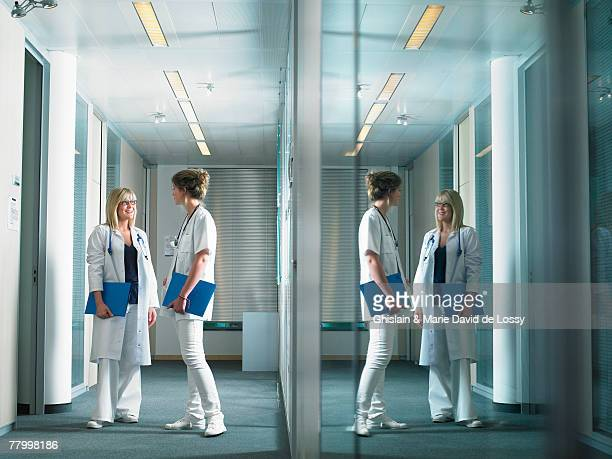 Two female doctors in discussion in a lobby of a hospital. Reflection on glass wall.