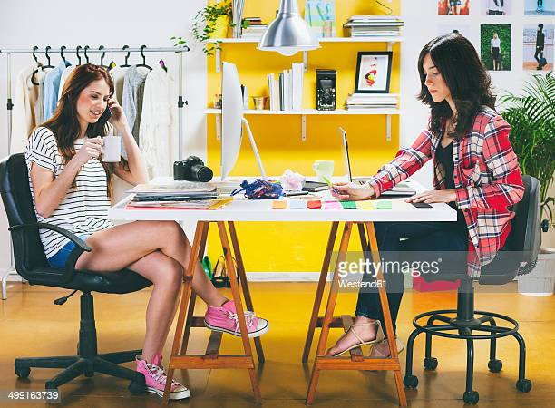Two female fashion bloggers sitting at desk in the office