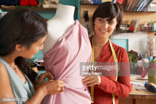 Two female fashion designers dressing mannequin in studio, smiling : Stock Photo