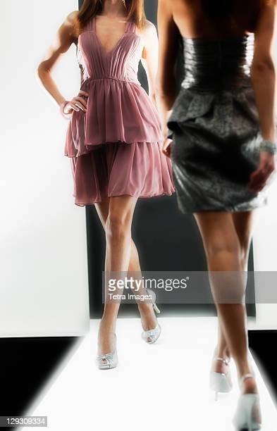 Two female fashion models wearing dresses on catwalk